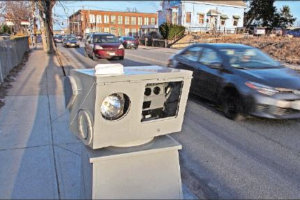Speed camera set up on sidewalk with city in background