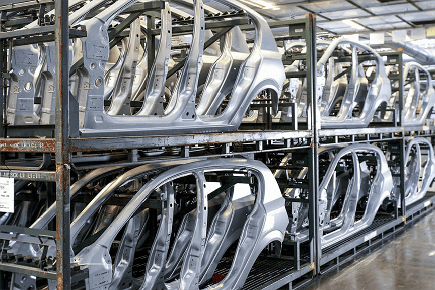 Silver car frames lined up and stacked in a warehouse ready for assembly