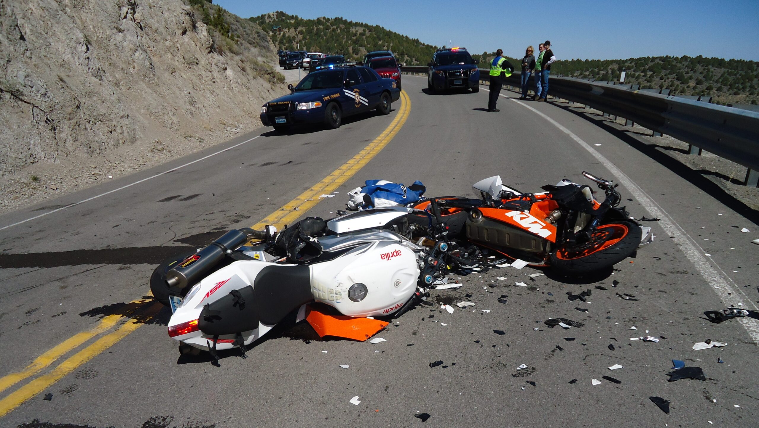 Motorcycle accident in RI with motorcycle laying on road with police around it and damage to the motorcycle
