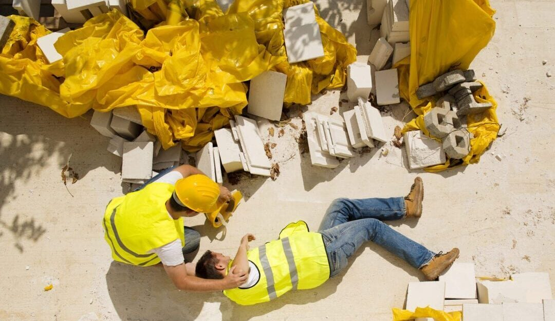 Constuction Accident in RI where man in yellow vest falls from scaffold while another construction worker helps him in Rhode Island